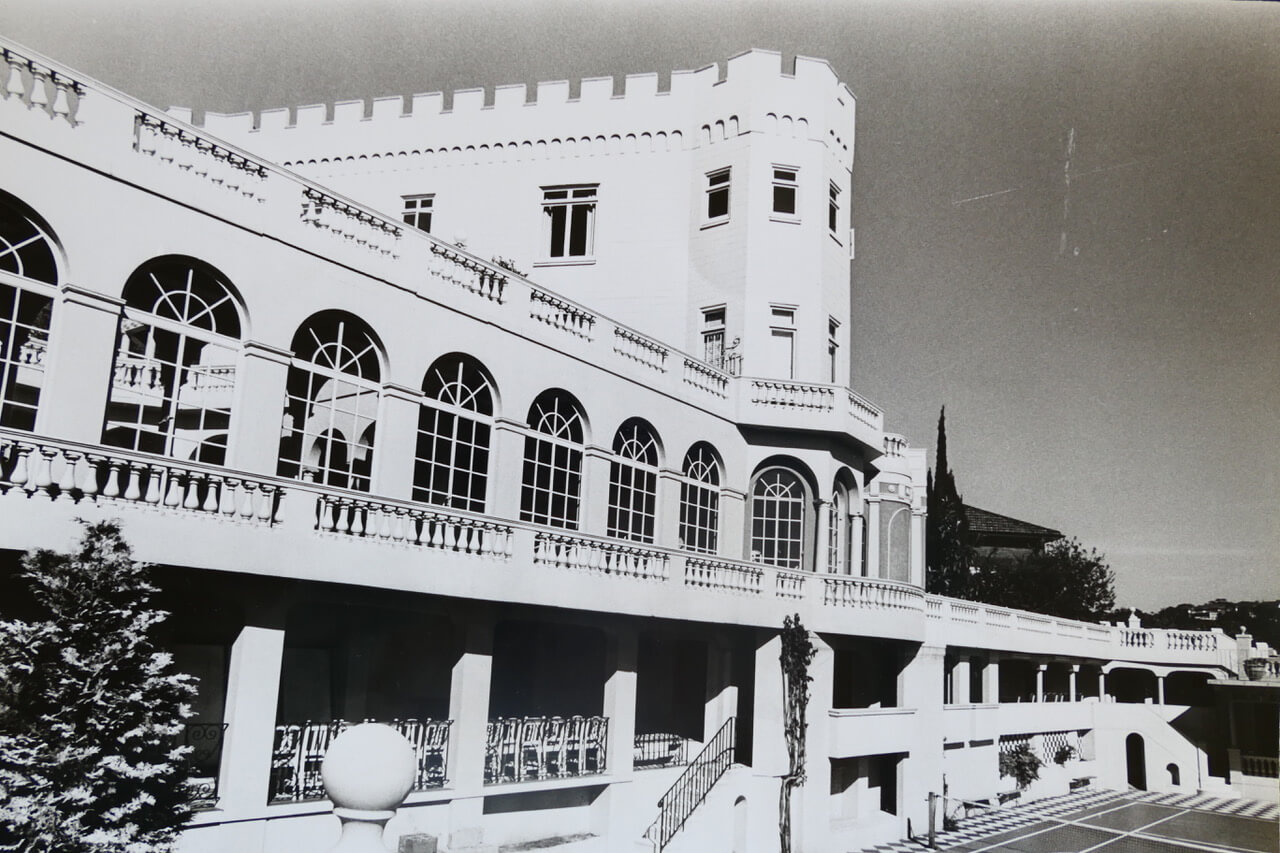 Full length arched windows of the theatre overlooking the tennis court.jpeg