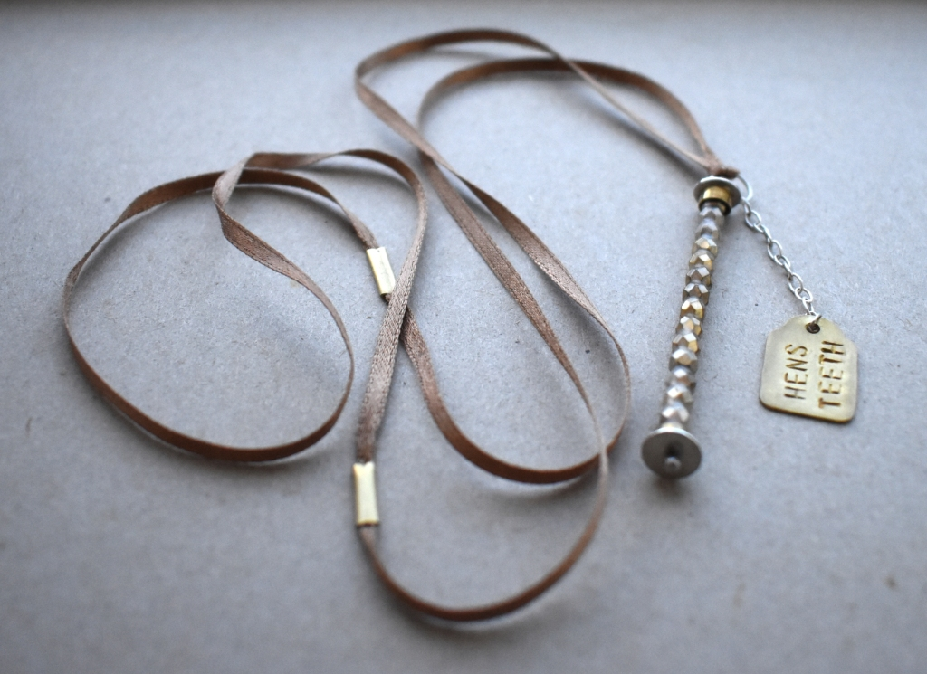 DAY 1: Caroline Thomas, Hen's Teeth Charm (Sterling silver, brass, glass beads, heat shrink tube, ribbon)