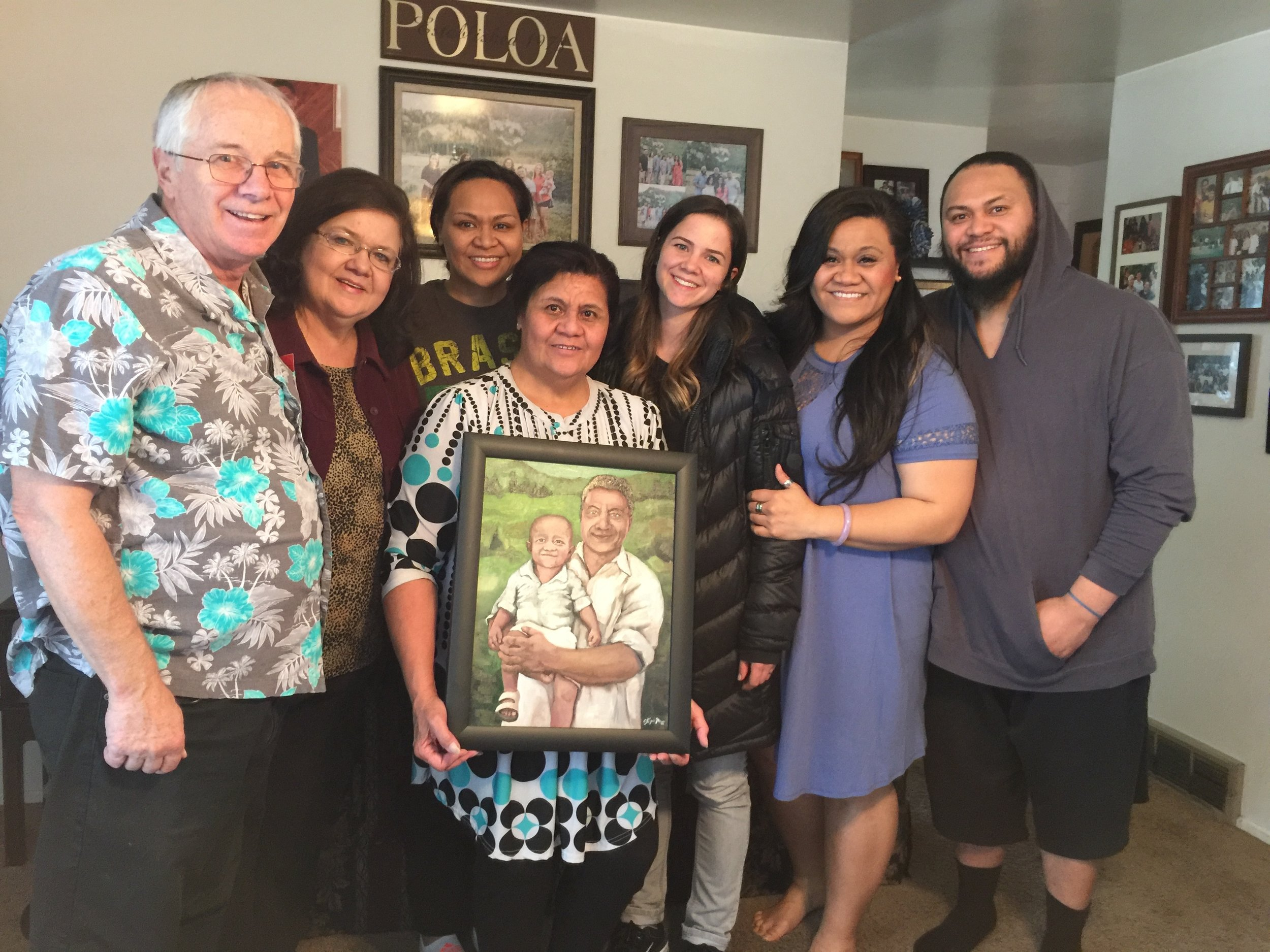 This is my parents and I giving the painting and poem to the Poloa family.