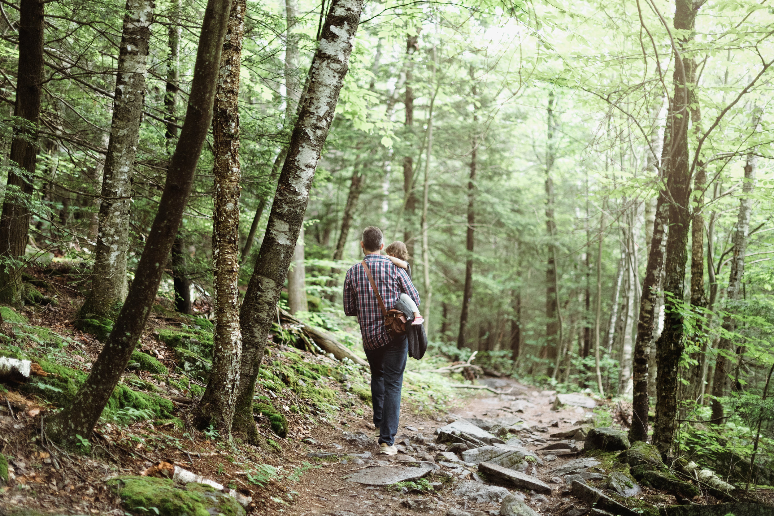 father carrying his daughter through the woods on a hike