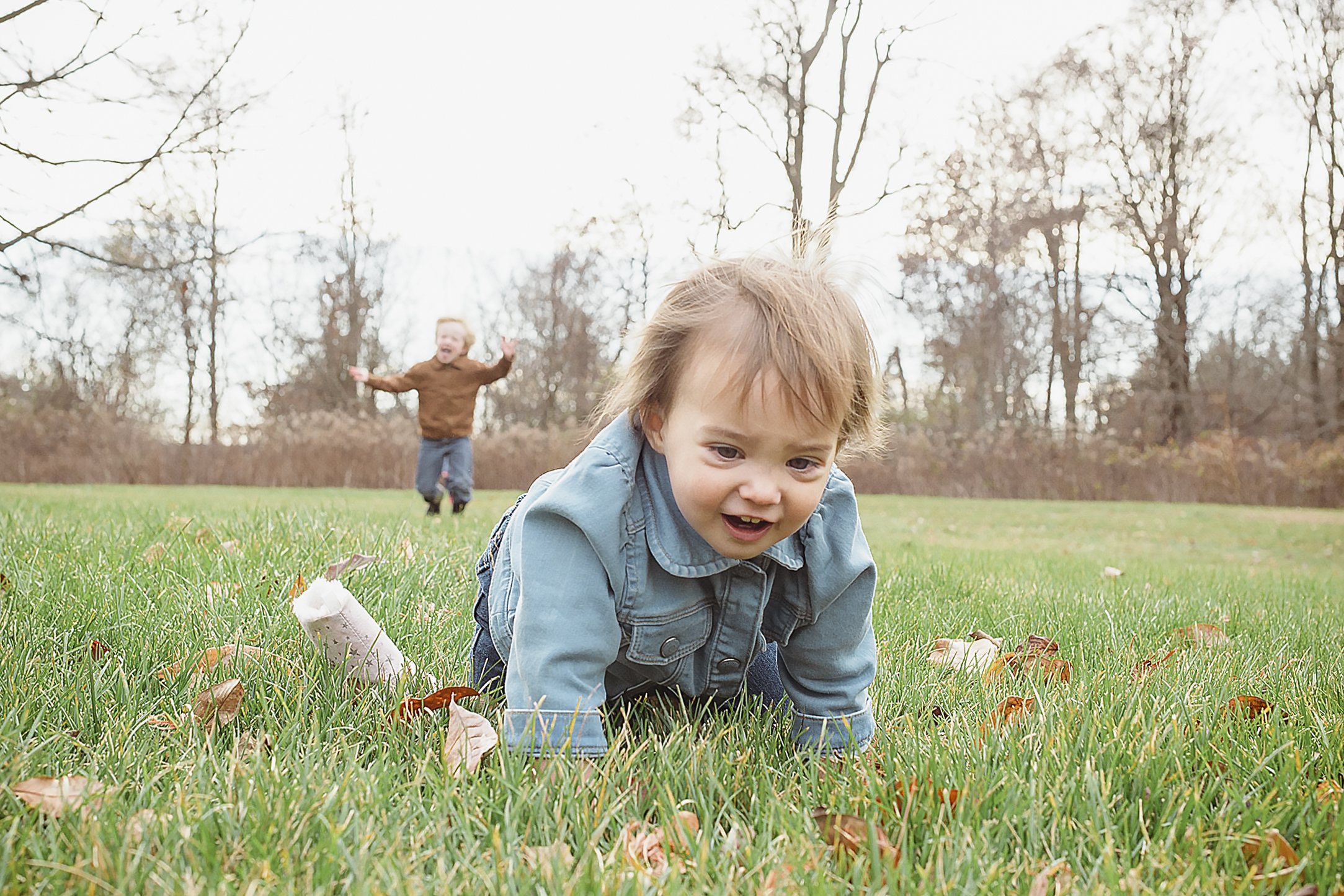 young child crawling through the grass as her brother is running up behind her.jpg