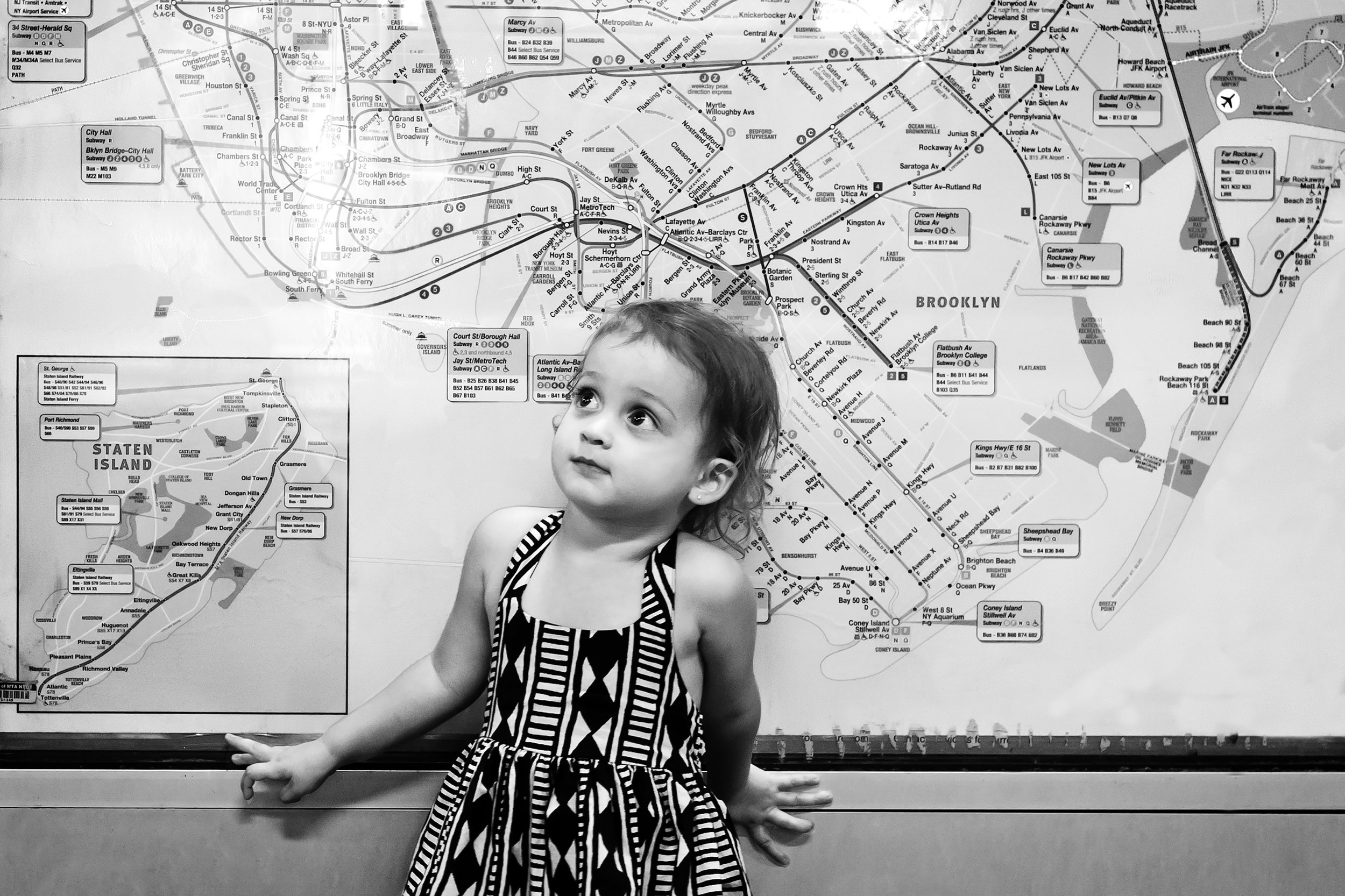 black and white image of a young girl standing in front of NYC Subway map.jpg