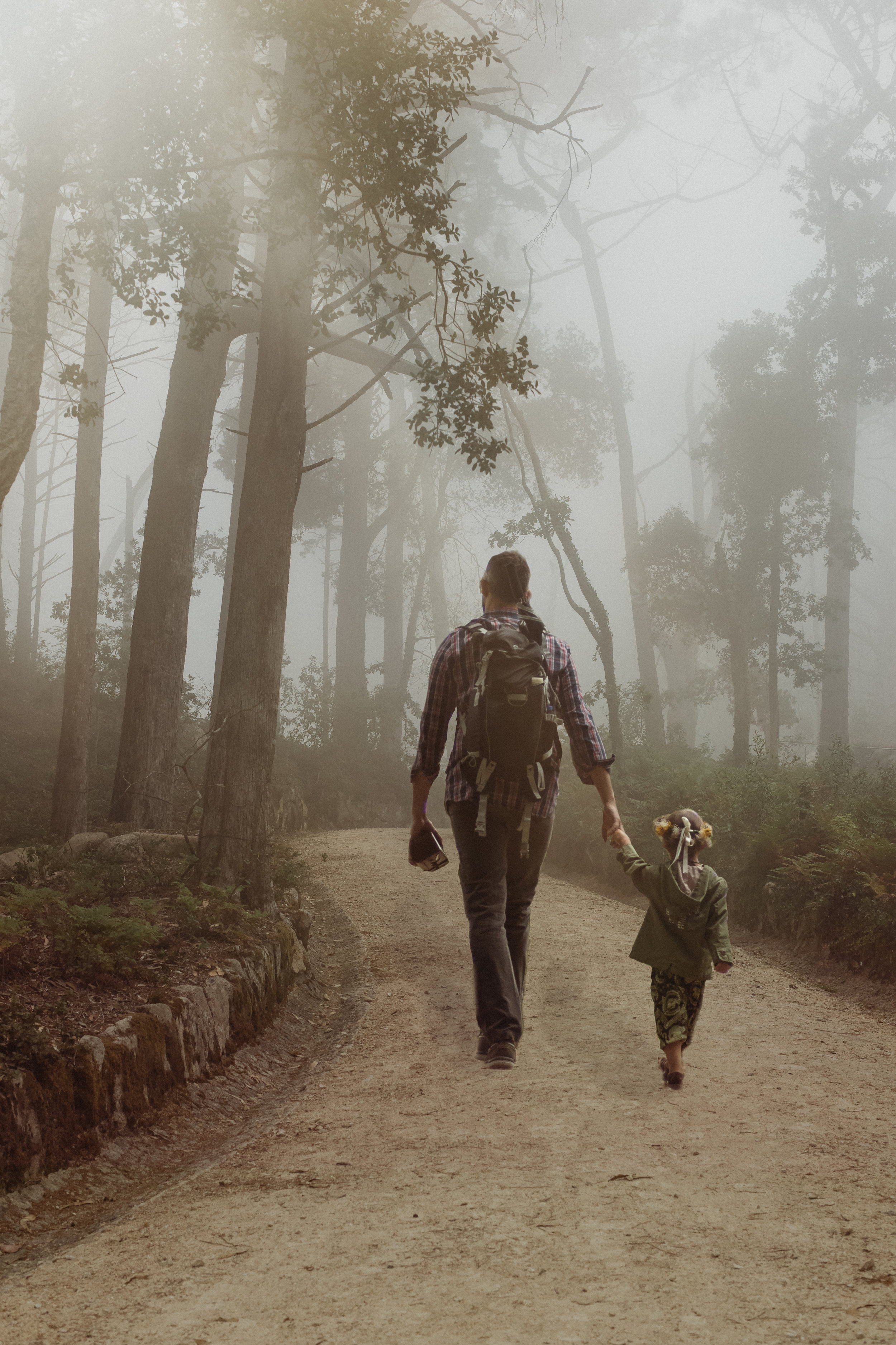 father walking hand and hand with his daughter through the foggy forest