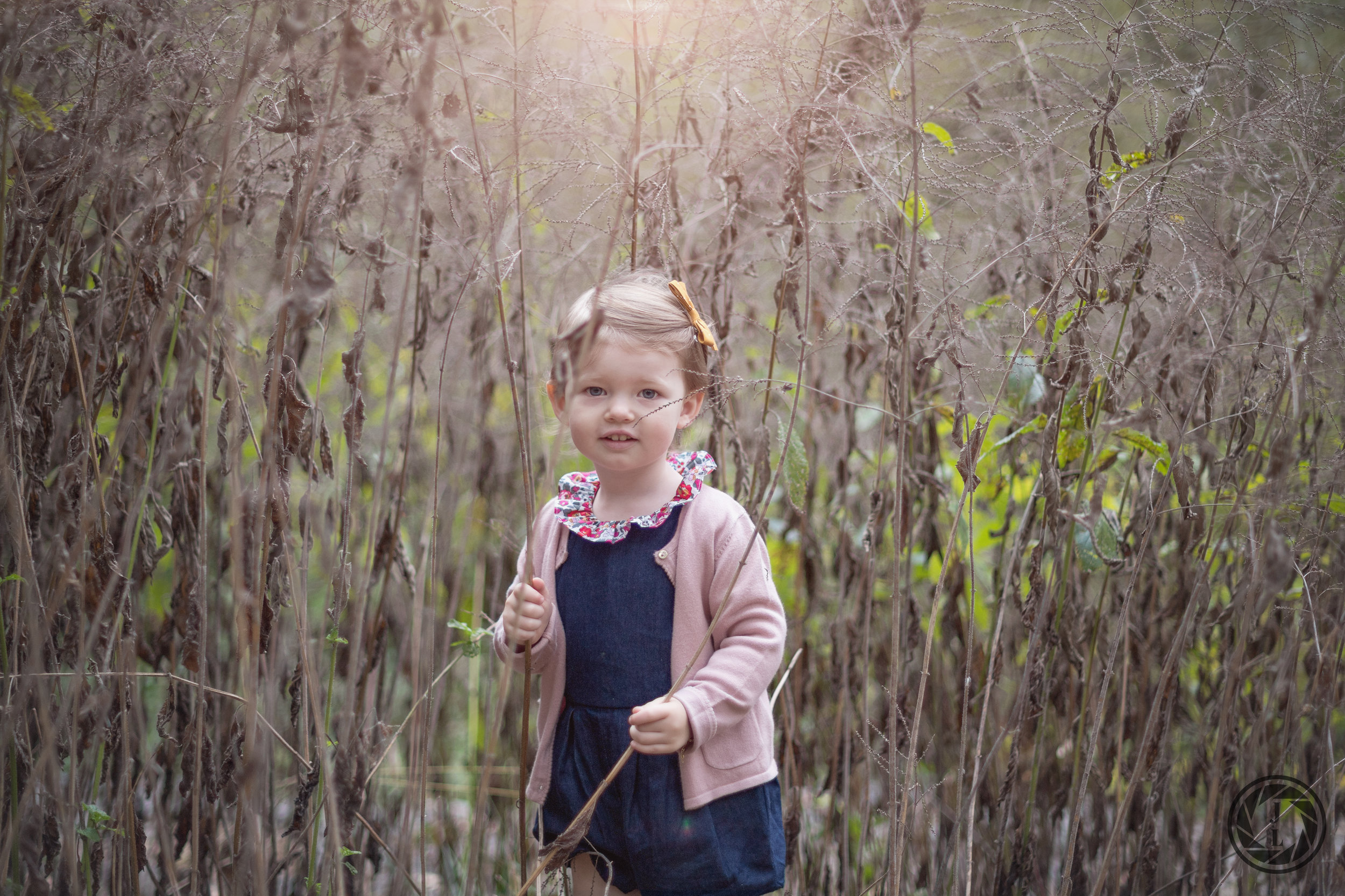 young girl smiling at the camera in tall grass