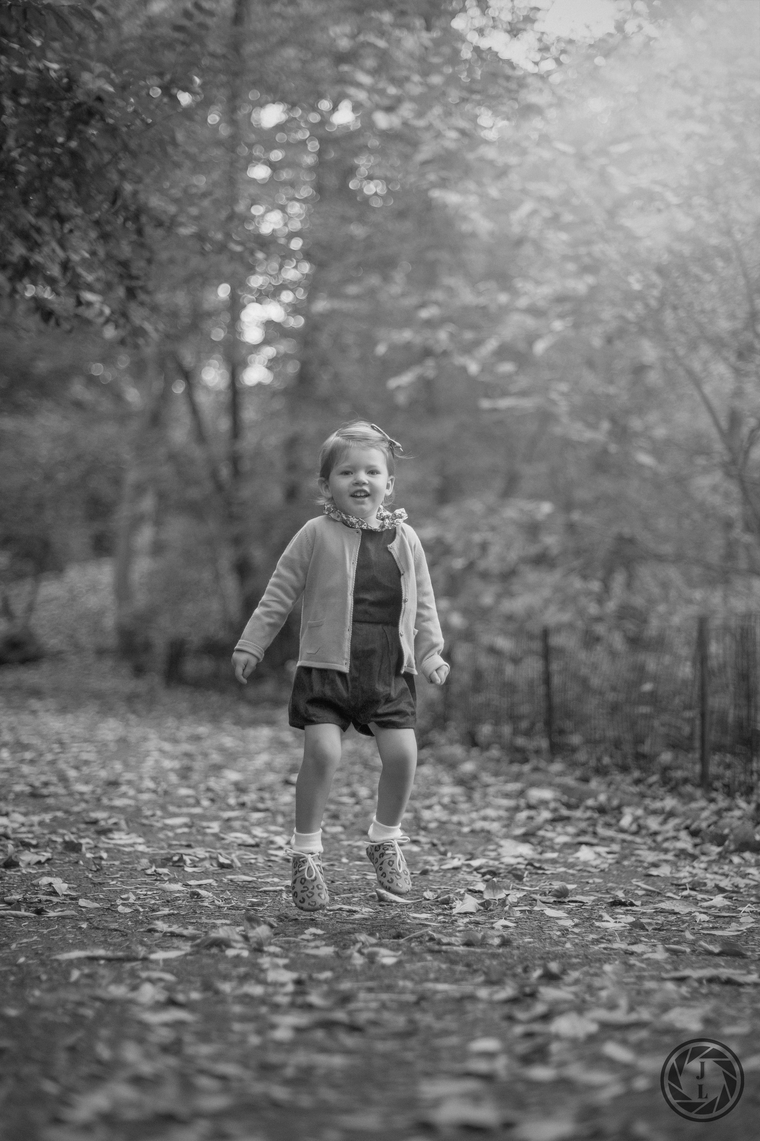 black and white image of a young girl jumping in the air in the park