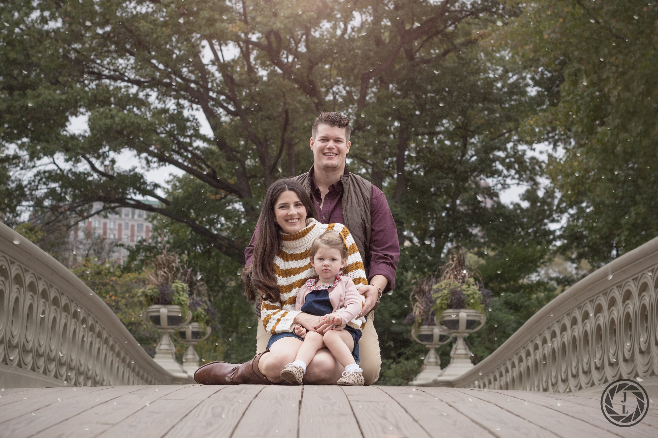 color image of smiling family on a fall day sitting on the bridge