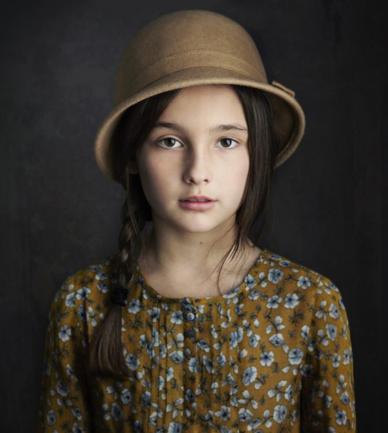 A tween wearing a beautiful olive dress and hat.