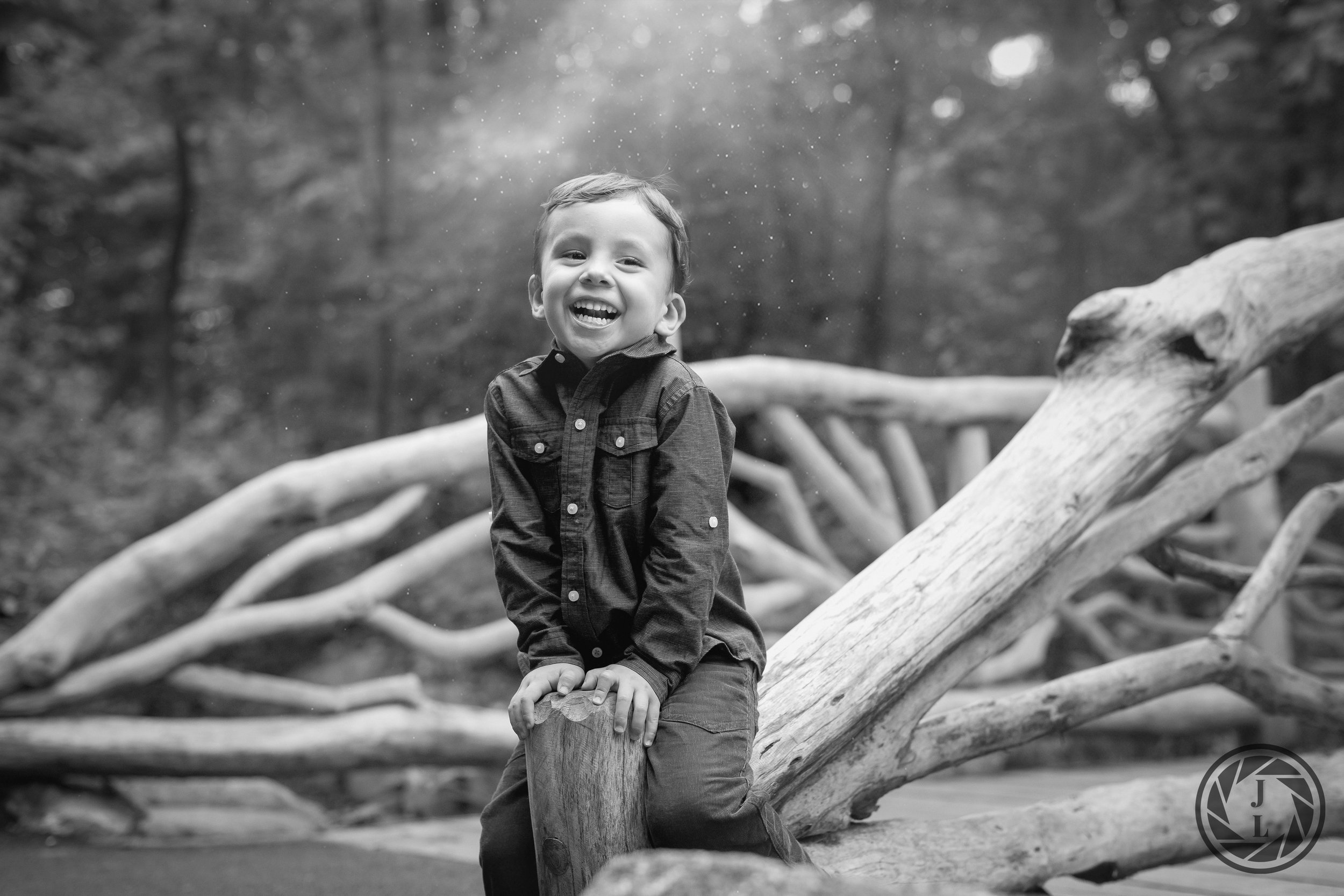 black and white image of a laughing boy sitting on a wooden bridge