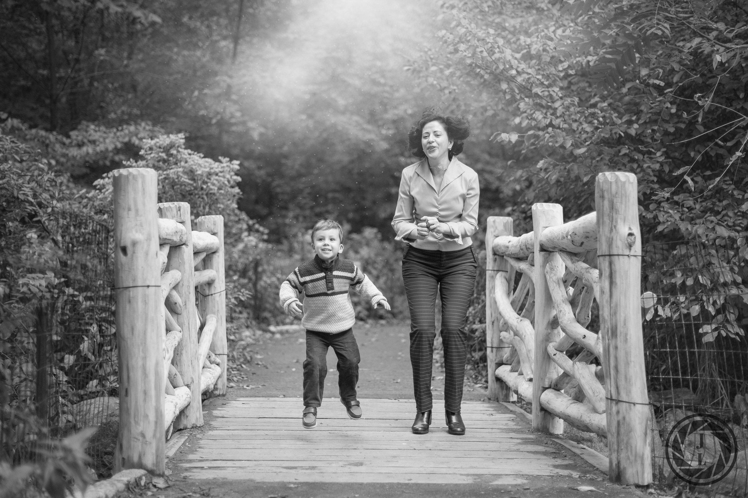 black and white image of mother and sun jumping up in the air on a wooden bridge