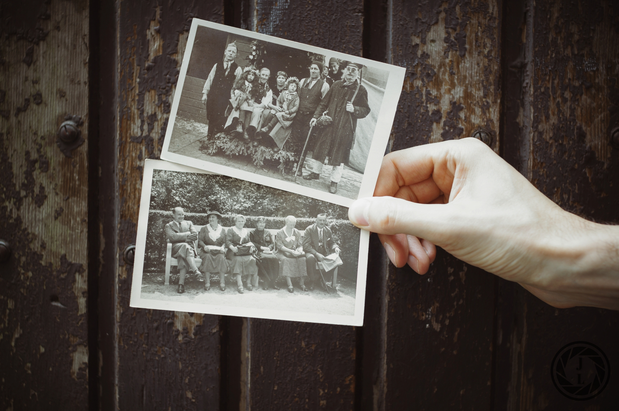 image of a hand holding two black and white pictures of older families