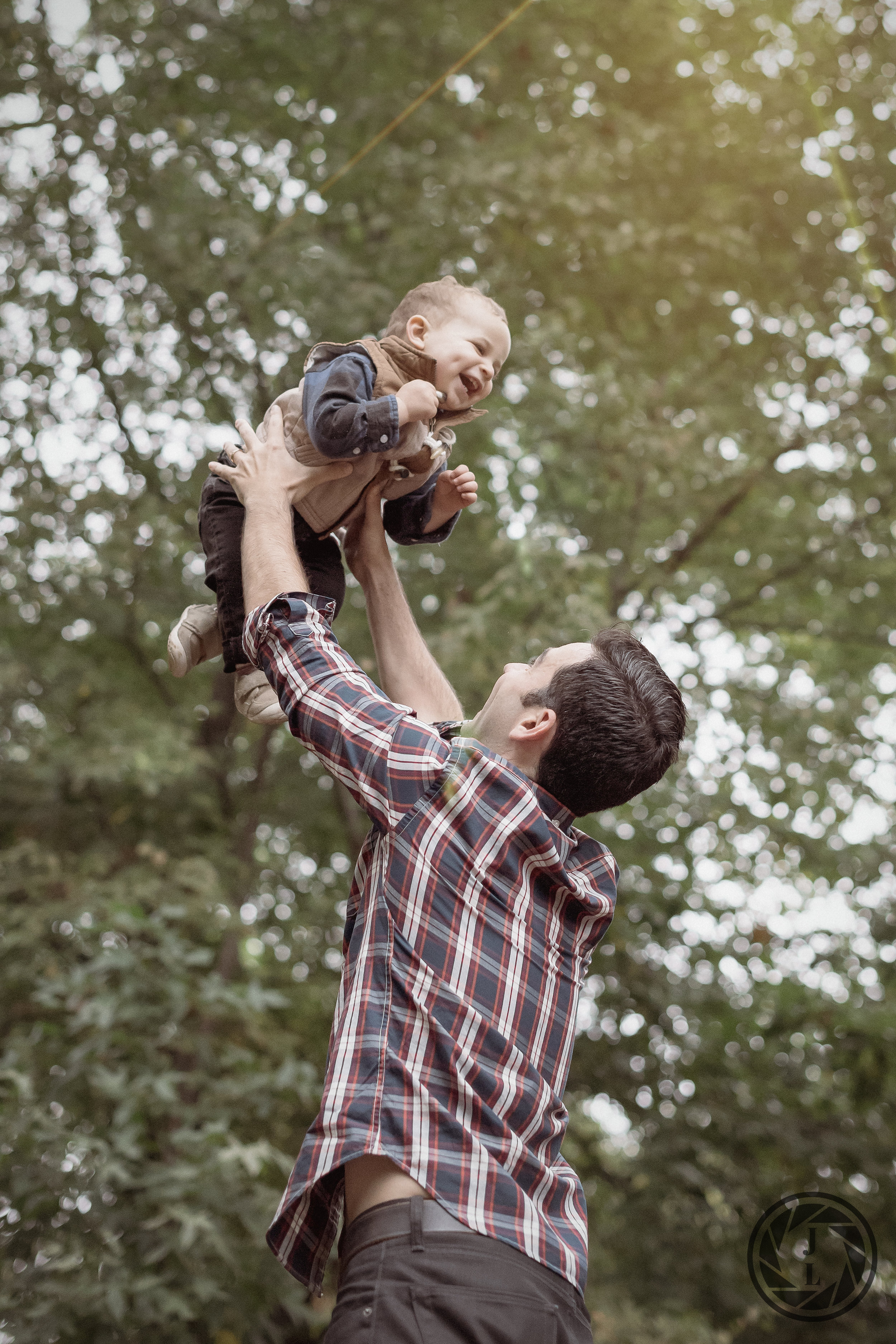A father tossing his laughing son in the air