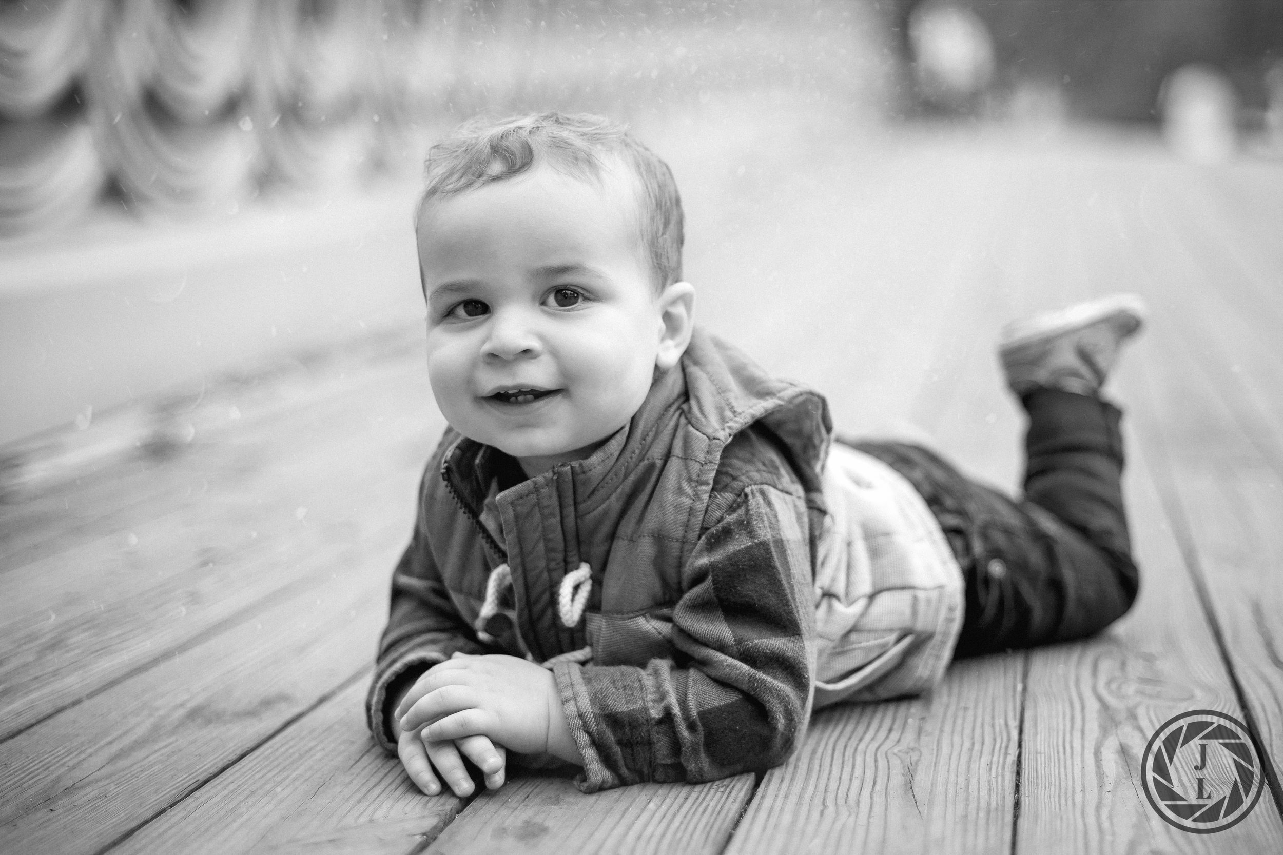 A little boy smiling and posing on his belly with his feet in the air