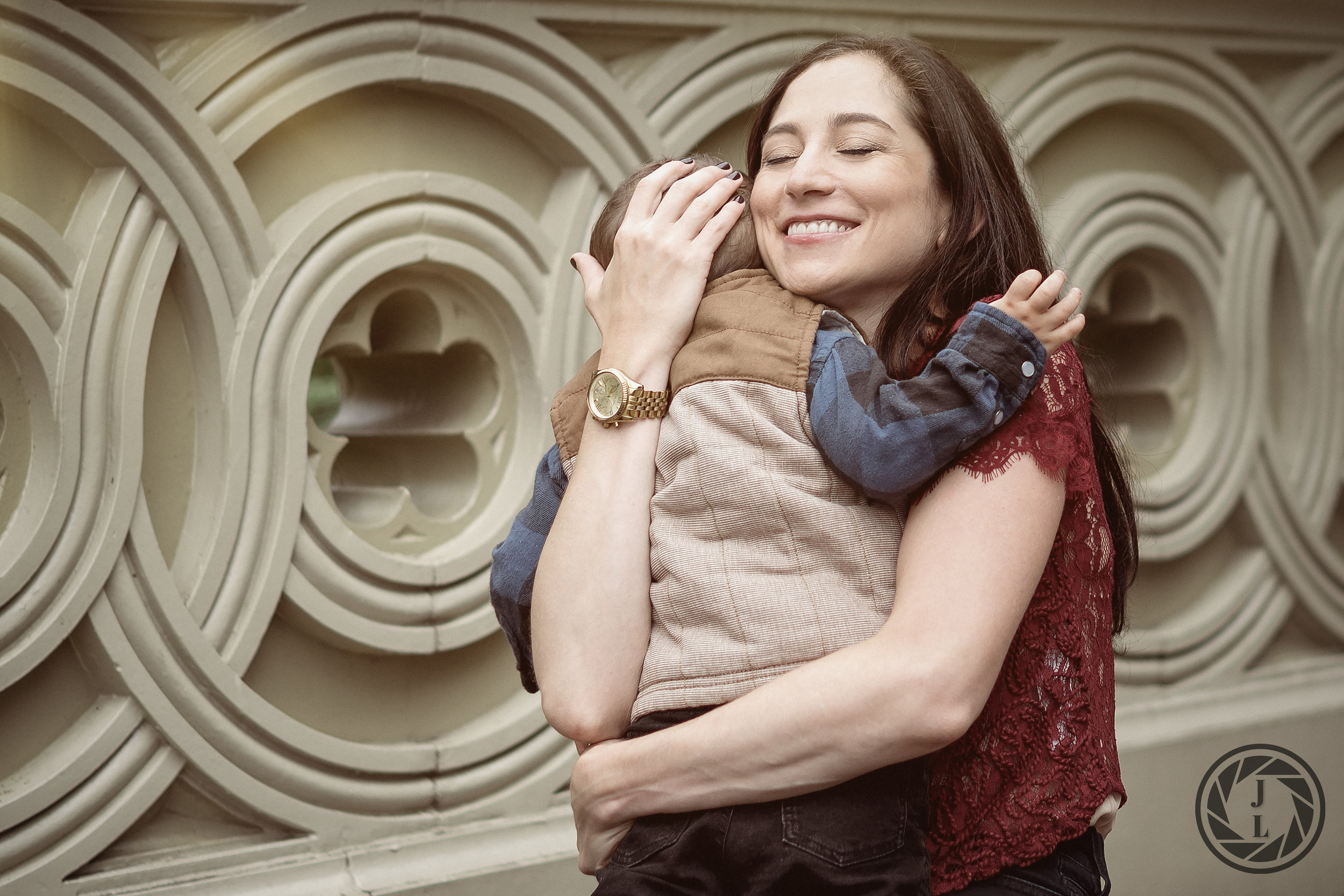 A mother embracing her son and smiling with her eyes closed