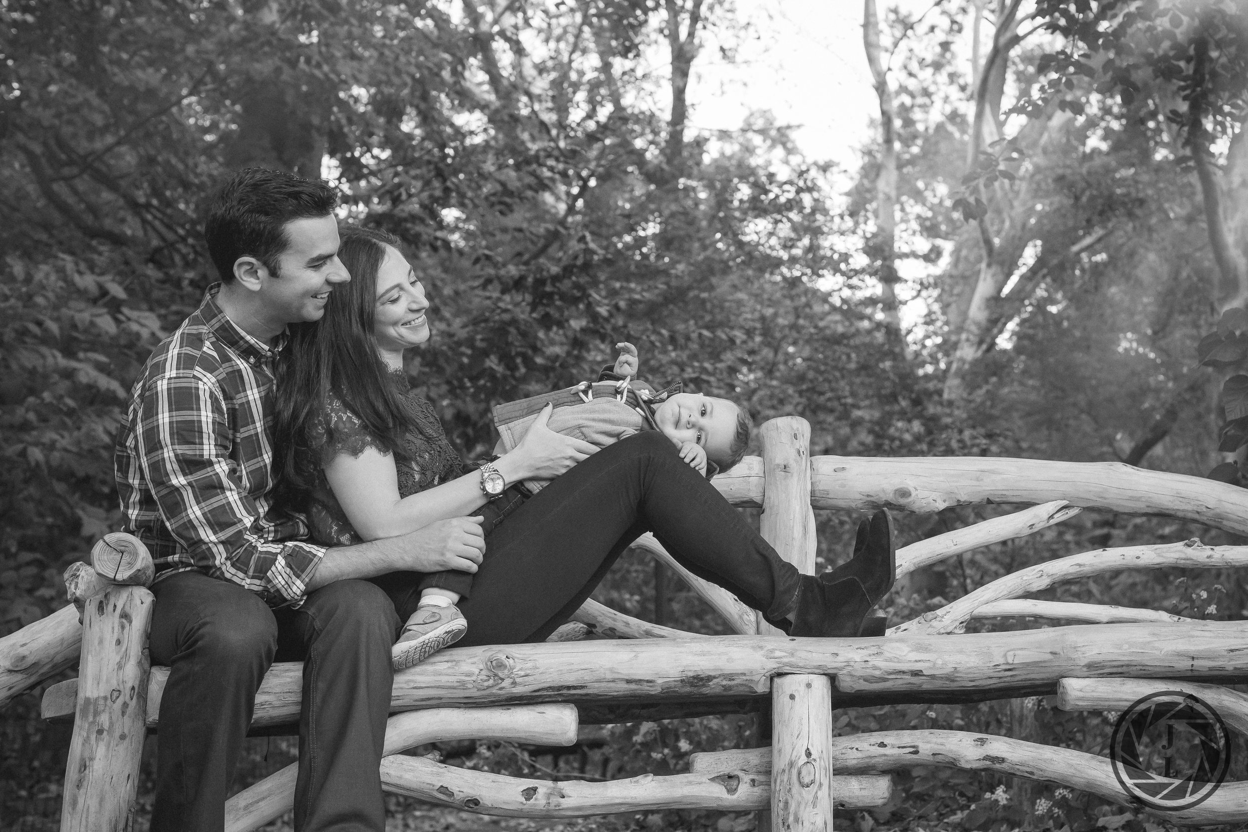 A family of three laughing in a candid pose on a park bench