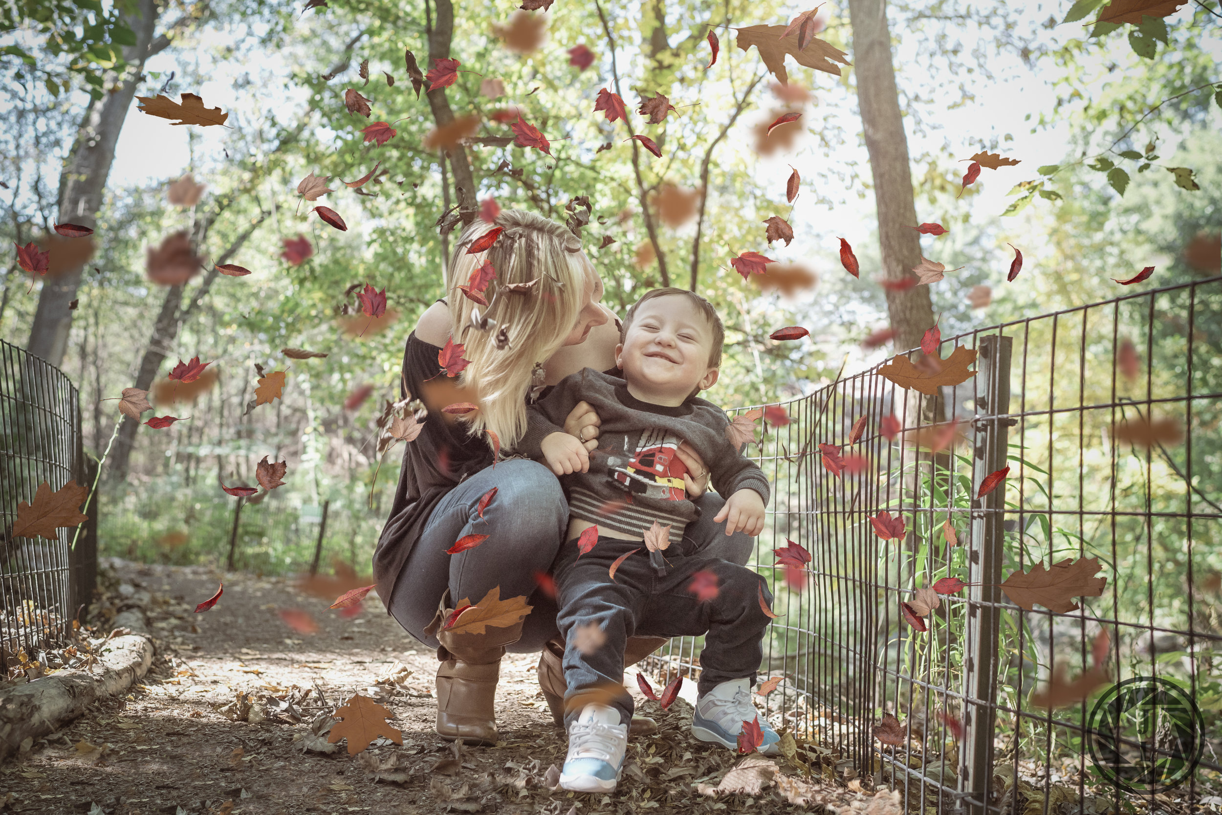 A mother and son laugh and leaves fall around them in Central Park