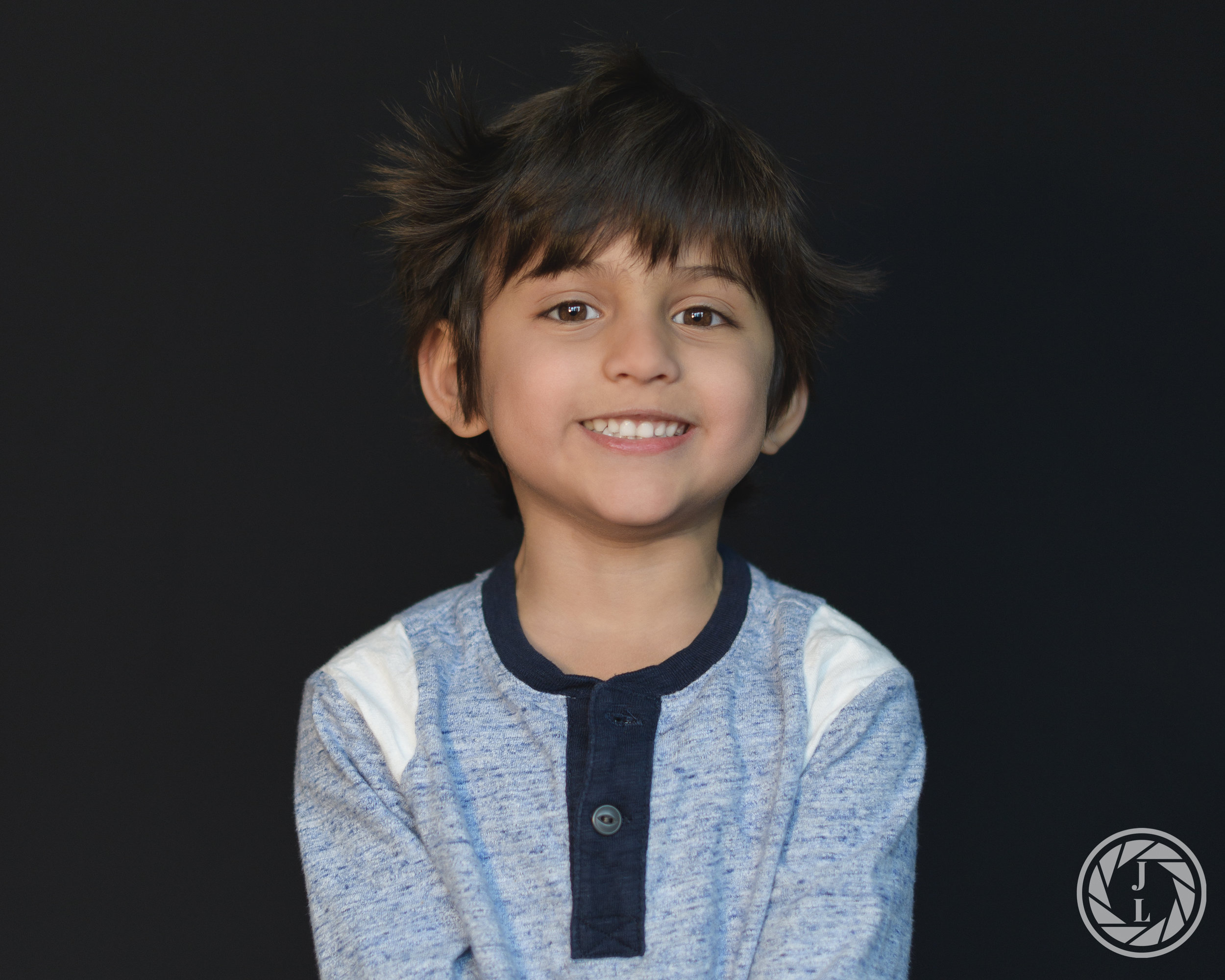 A happy, toddler smiling and looking towards the camera with messy hair.