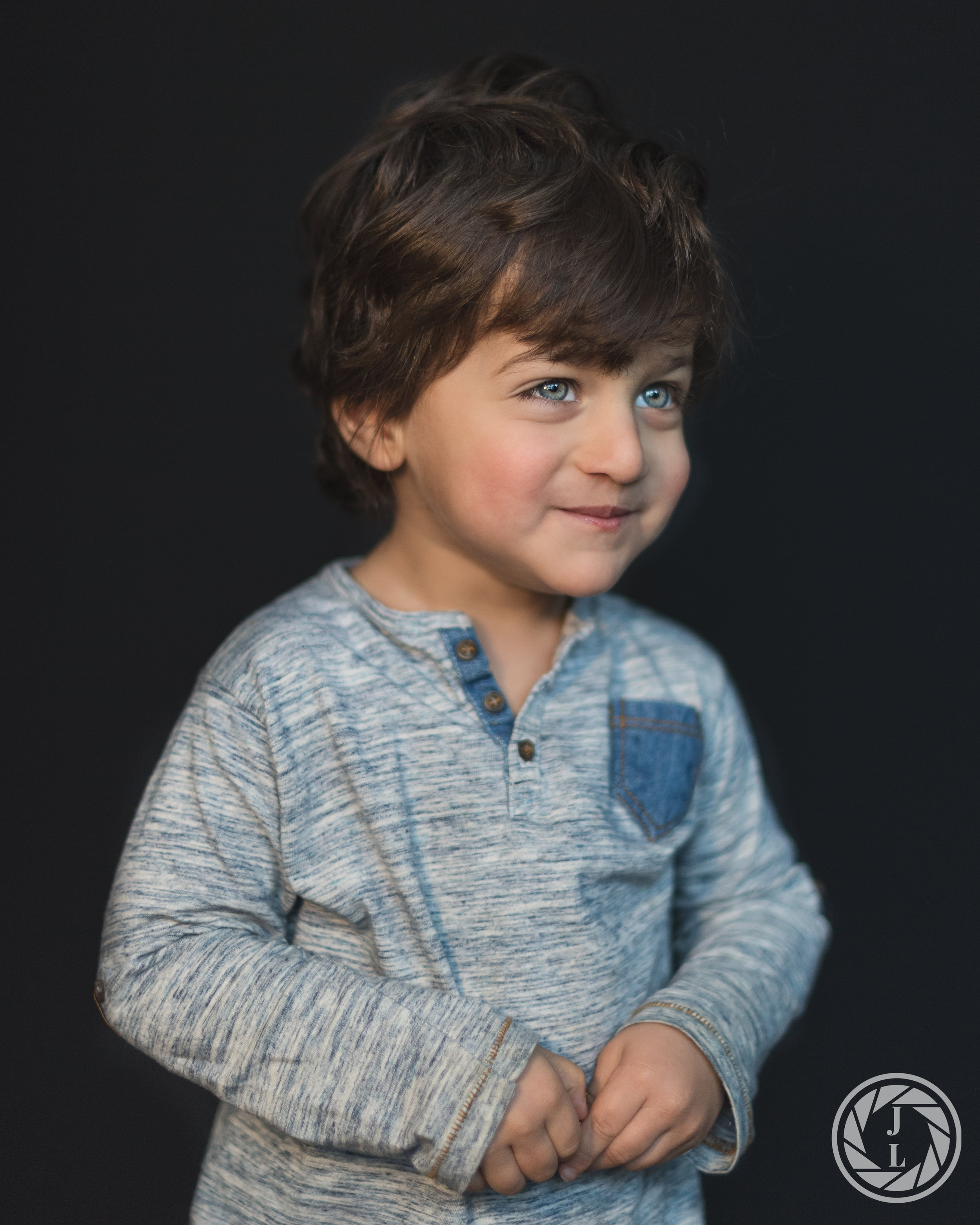 A young toddler with bright blue eyes starring off to the right of the camera with his hands held together.