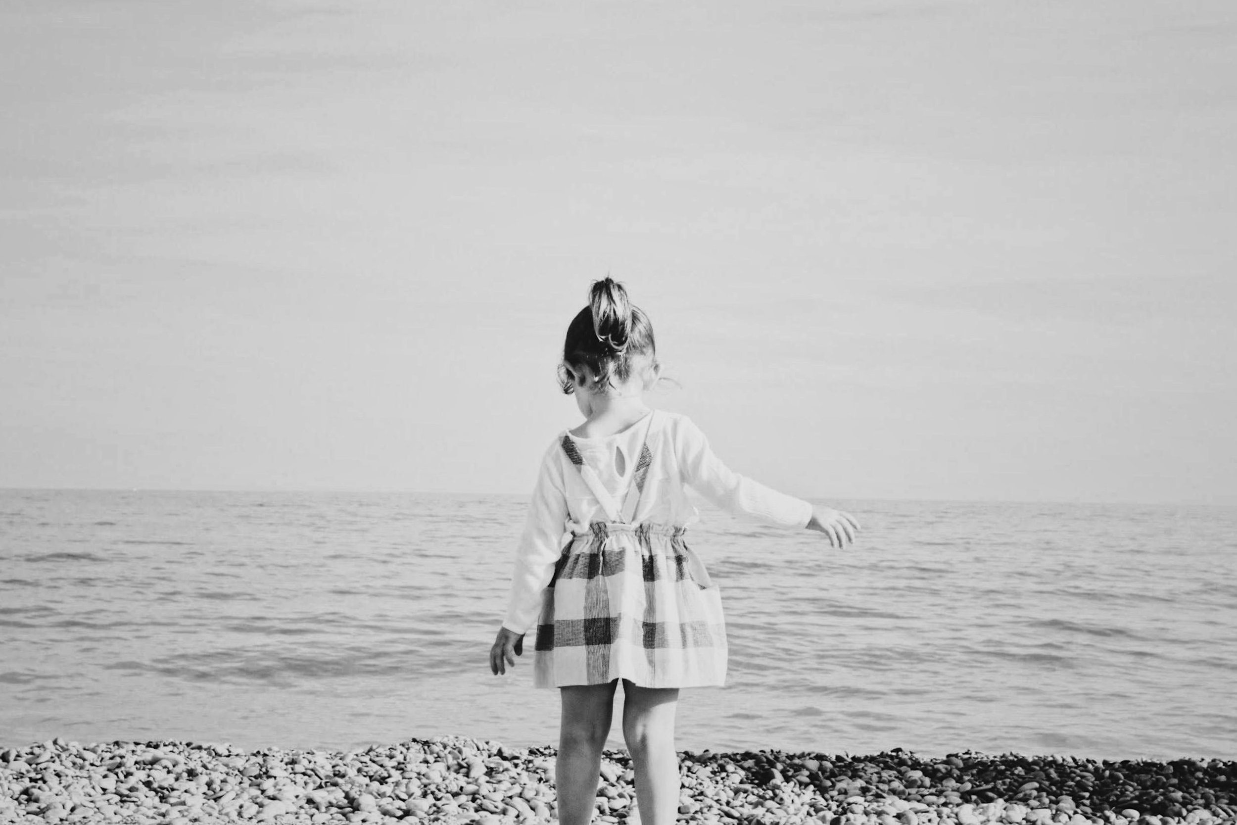 A black and white photograph of little girl starring at the ocean from the beach.