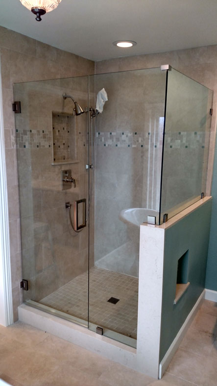 A frameless shower enclosure with a return panel in a brushed nickel finish.