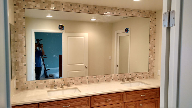 New bathroom vanity mirror with custom lamp fixture cutouts.