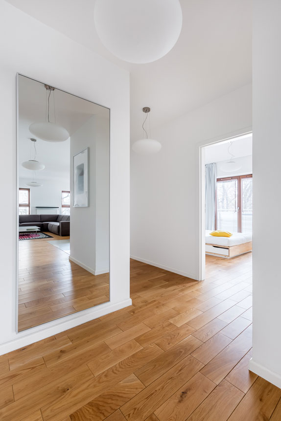 """A framed 1/4"""" mirror wall mounted in an entryway, increasing the perception of space in the hallway."""