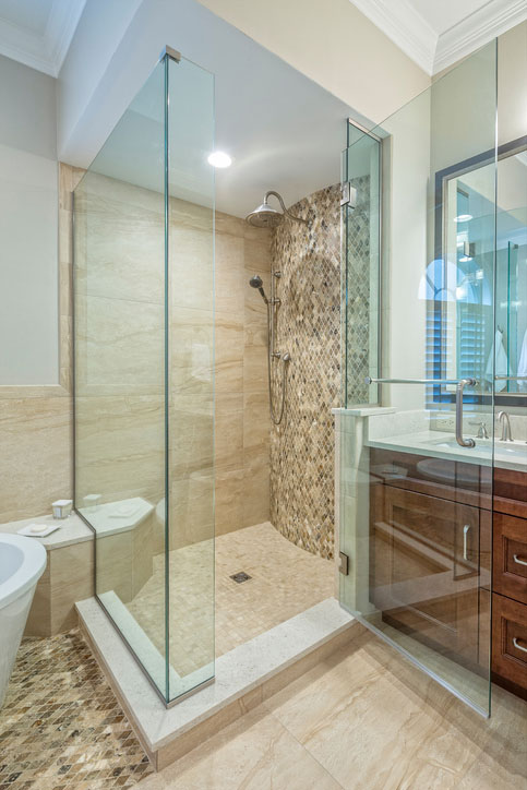 A frameless shower enclosure with bench seat and return panel using chrome U-channel.