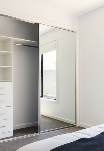 Chrome framed sliding wardrobe doors on a bedroom closet.