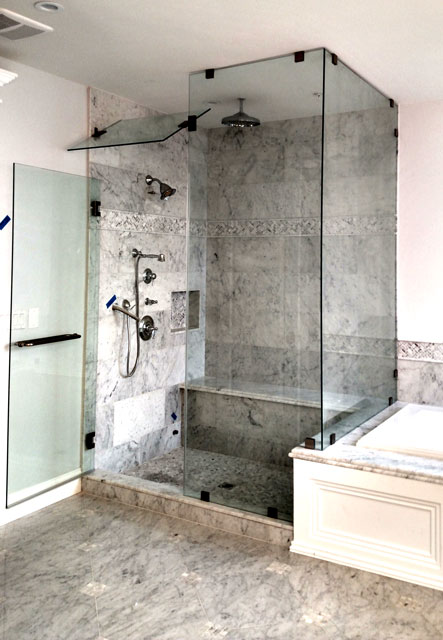 A heavy glass steam unit shower enclosure with a return panel and oil rubbed bronze hardware.