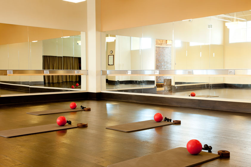 A yoga studio with wall to wall mirrors.