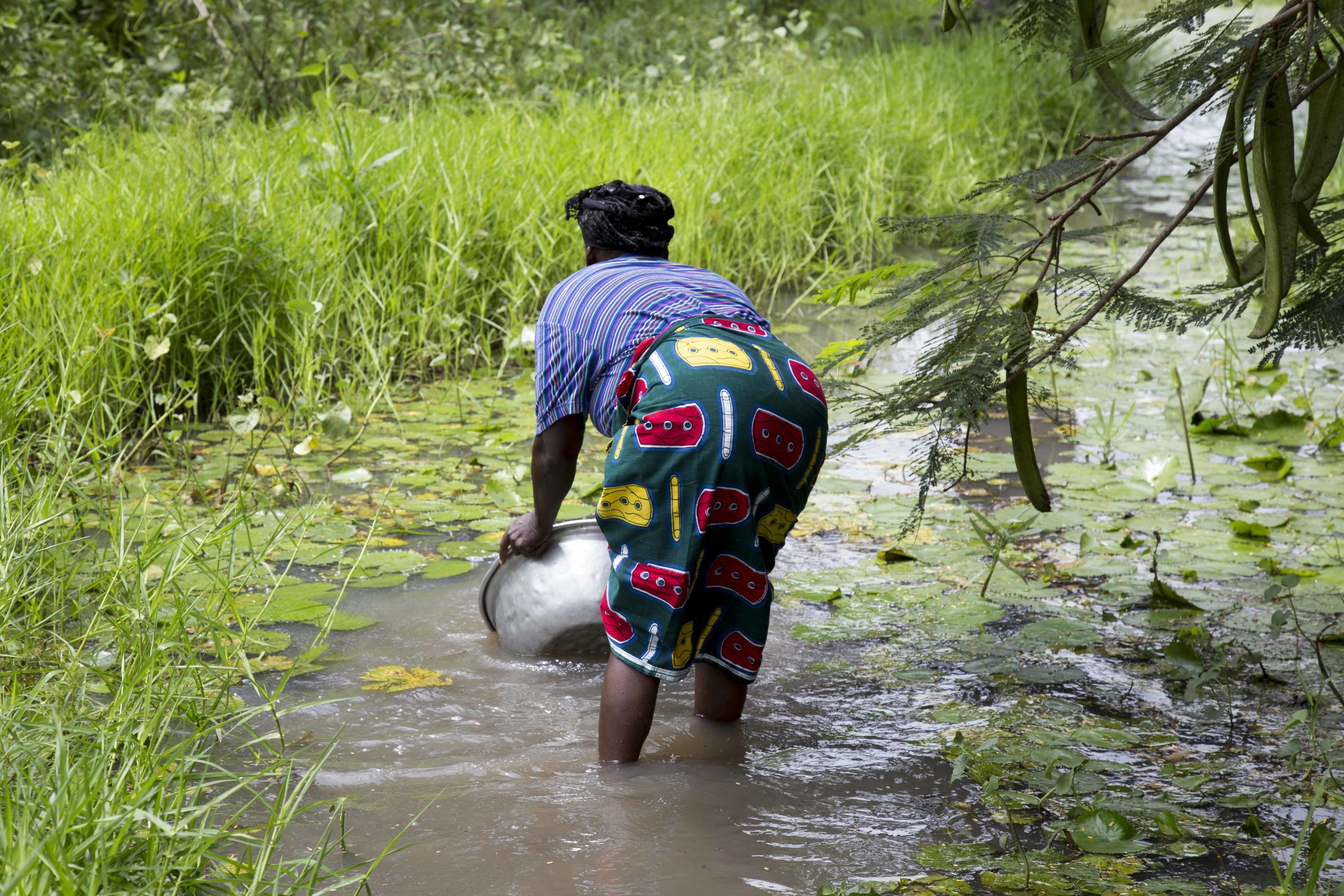 This image shows a woman getting water from a nearby river to their village.