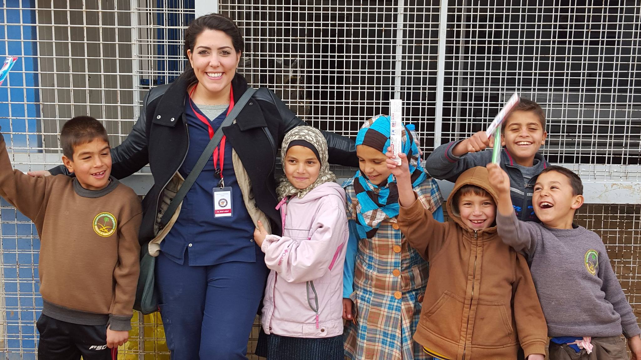January 2015 Mission trip at Al- Zaatari Refugee Camp on the Syrian- Jordanian Border: Dr. Lattouf hands out toothbrushes to her patients and laughs as they use them as swords while playing.