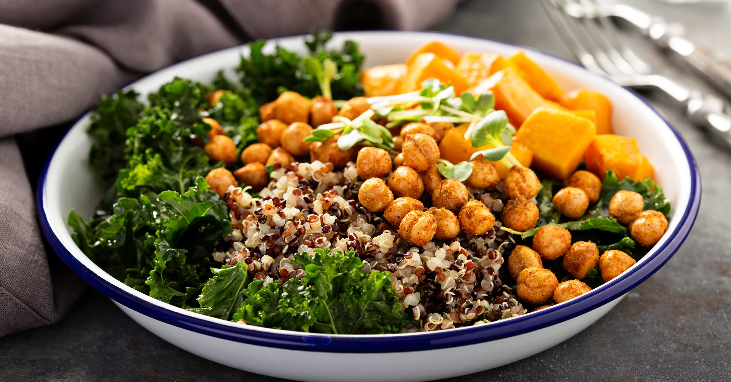 Plant-based lunch quinoa bowl, healthy vegan protein with lentils, beans, nuts, hemp seeds, and vegetables.