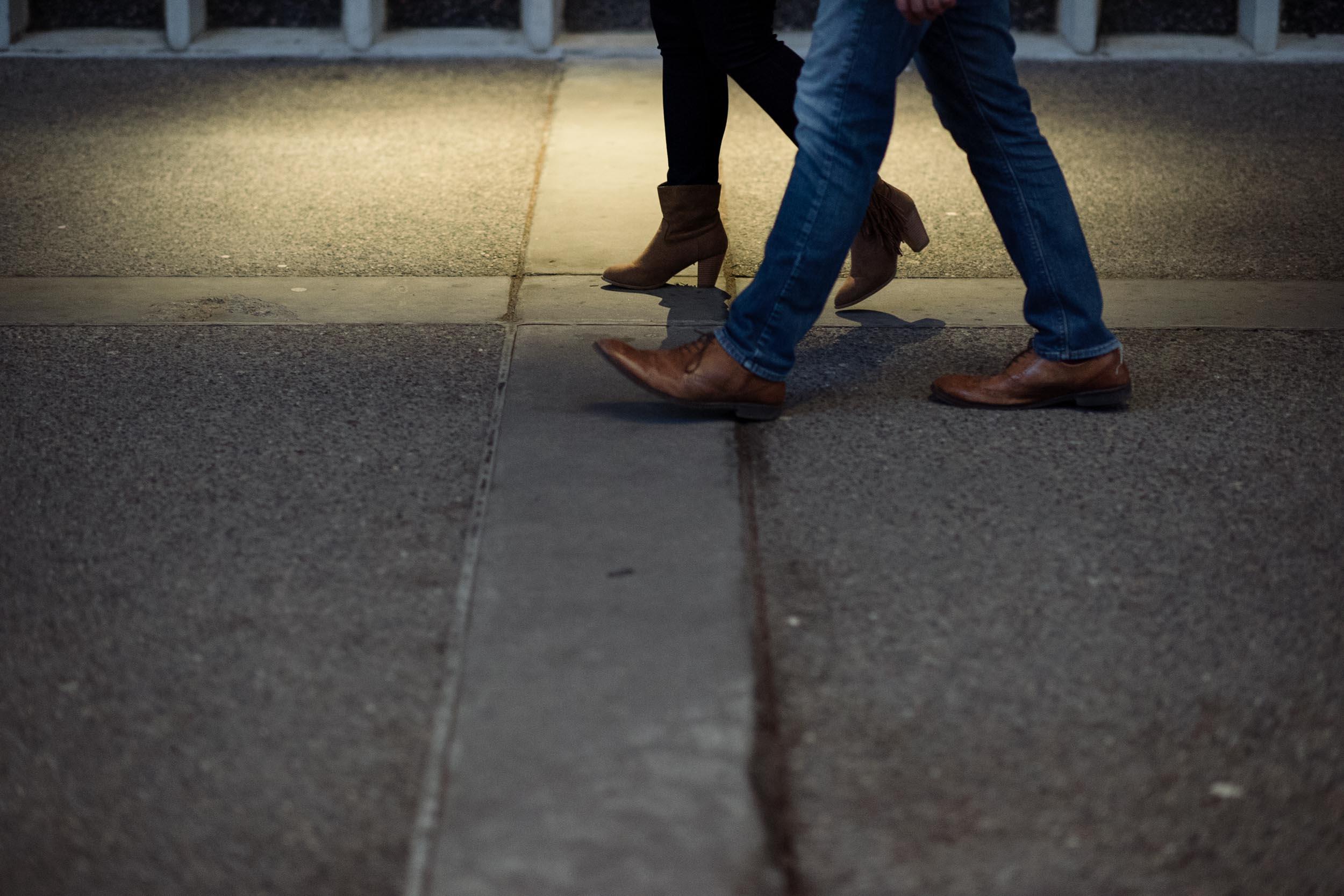 A man and woman's feet walking through a spot of light on a sidewalk.