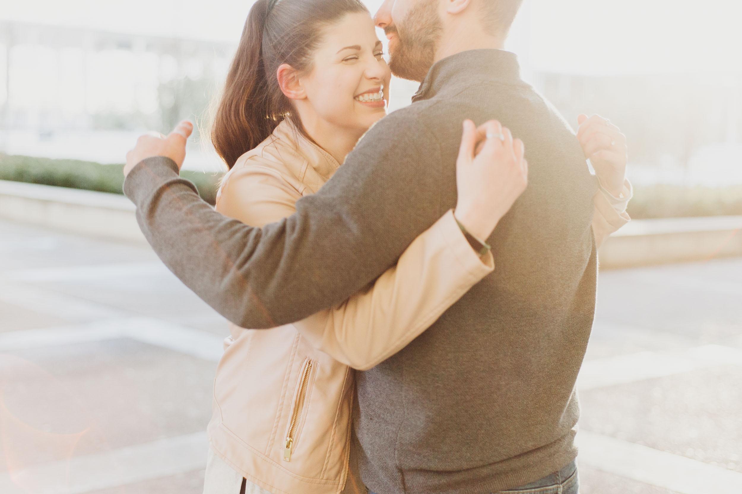 A young caucasian man and woman joyfully embrace as yellow orange sunlight wraps around them.