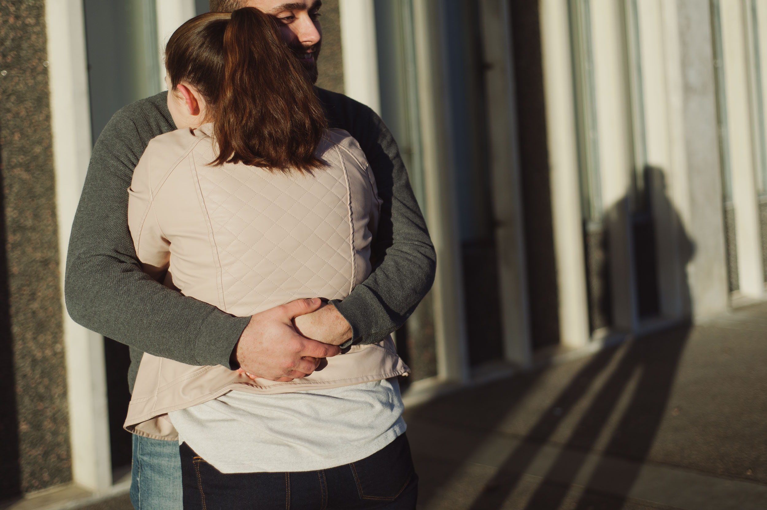 A young caucasian mand and woman embrace as the rising sun shines on them at the University of Albany campus.