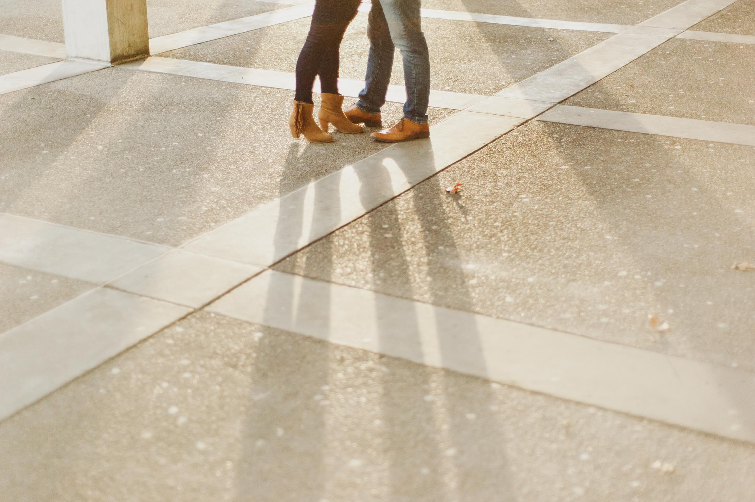 The feet of a man and woman are washed in light as the rising sun shines on them at the University of Albany campus.