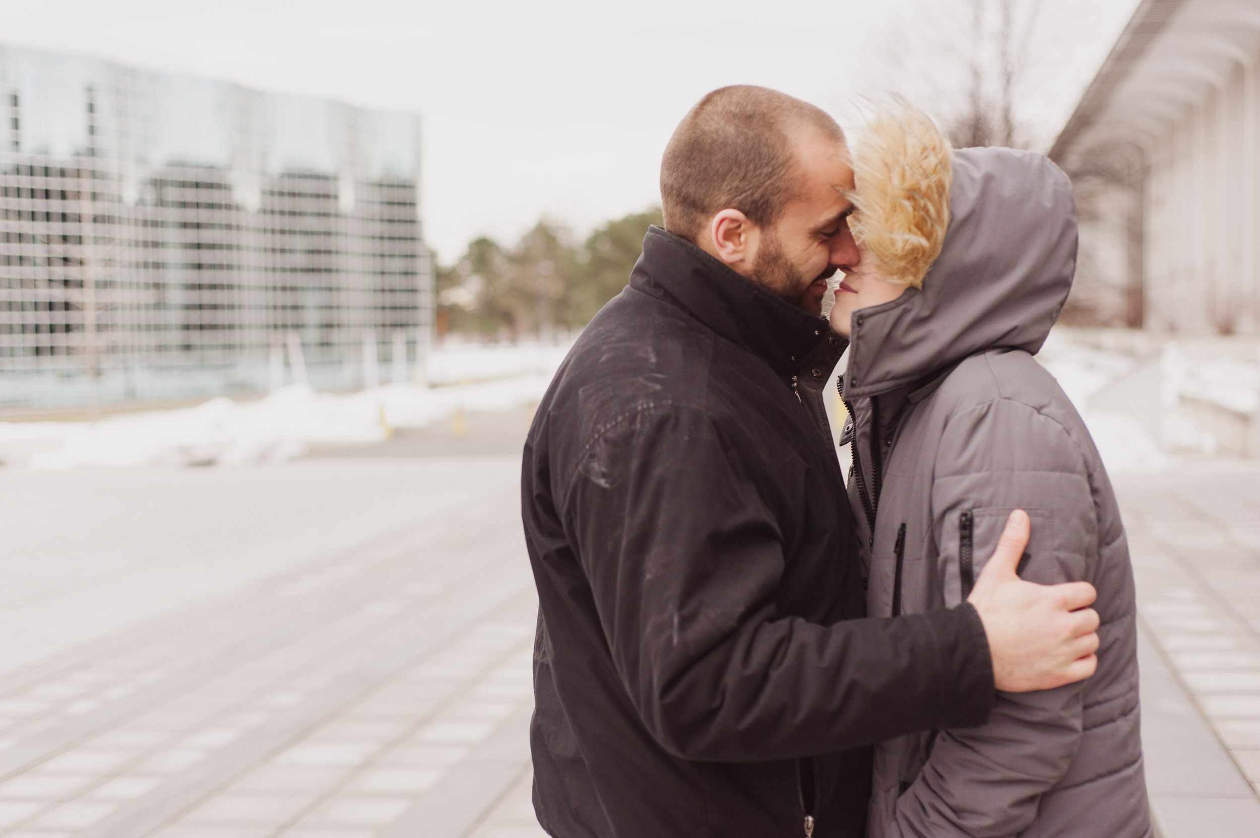 A young Caucasian man and woman, who are bundled up in warm coats, kiss as the rising sun shines on them at the University of Albany campus.