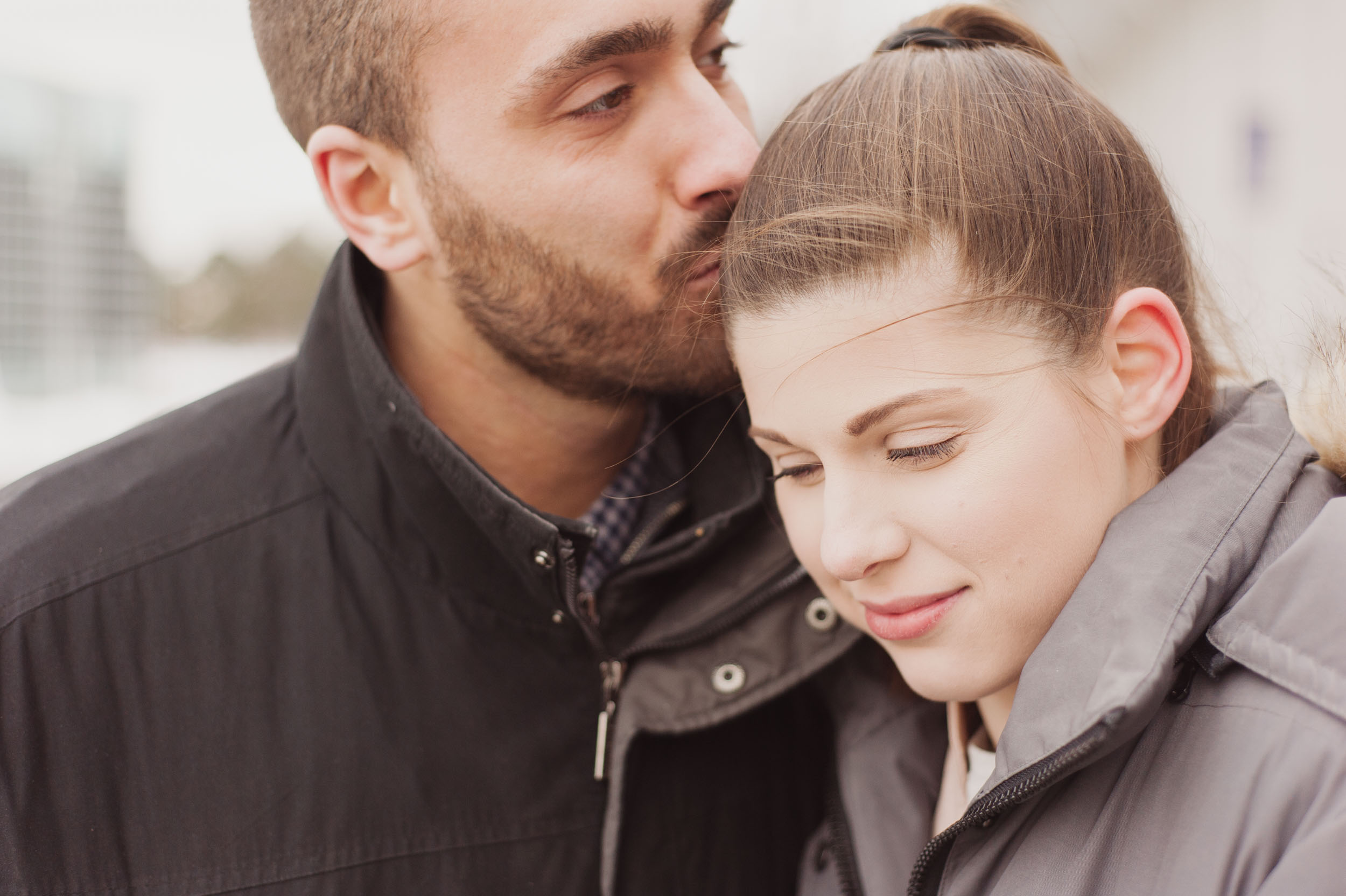 A close up image of a young Caucasian man kissing a young Caucasian woman on her head and she looks on content.