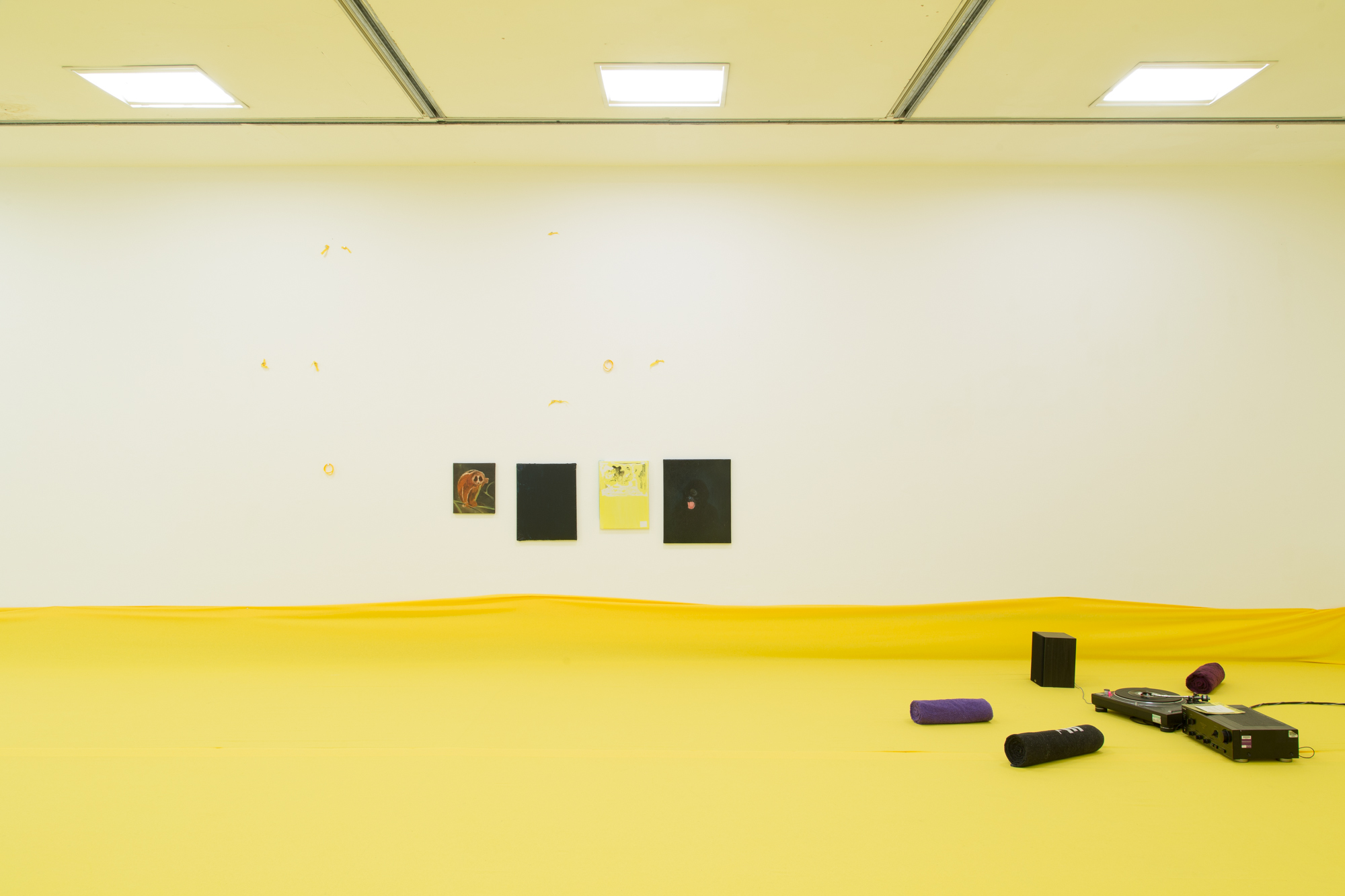 Installation view of 'Do U Feel Like We Do? at Intermedia Gallery, CCA Glasgow 2014. (Cotton, X-frame, photographic background, studio lights, towels, oil paint, turntable, amplifier, speakers, silicon gel bracelets, screws, inkjet prints, coins, plaster and video paint.) Photo: Tom Nolan