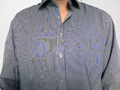 Moire pattern caused by the pinstripes in the shirt.