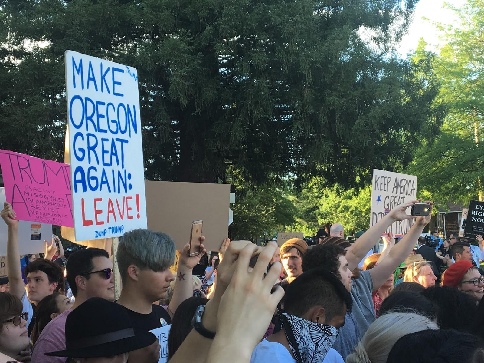 """Os protetastantes contra Trump seguram cartaz que diz: """"Faça Oregon Grande Outra Vez:Deixe-o"""""""