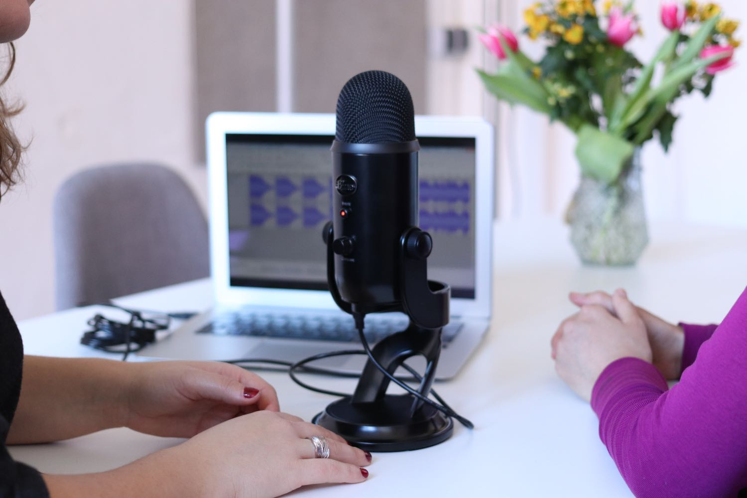 Two women sitting at a table with a podcast microphone between them