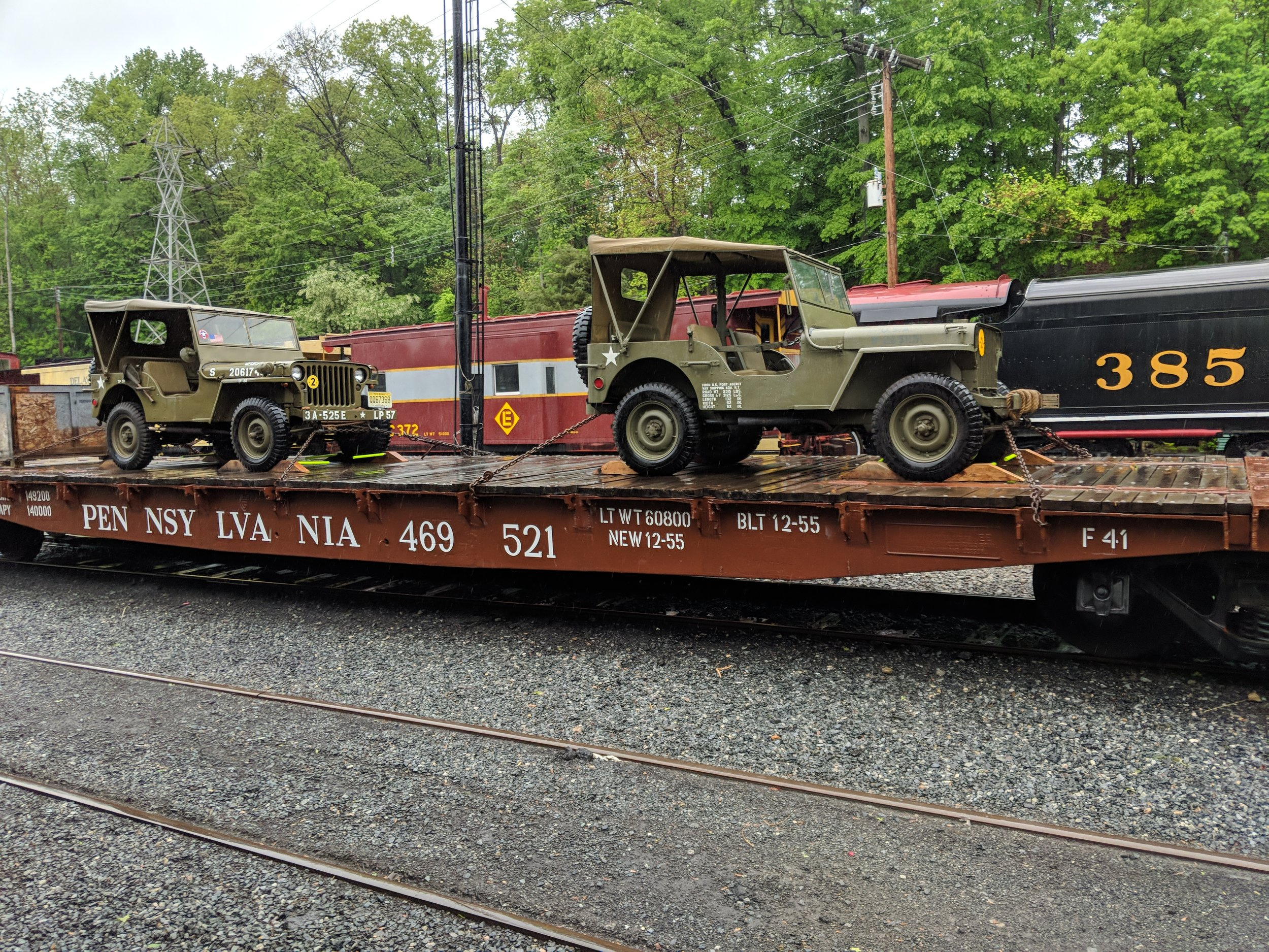 Two WWII Jeeps are tied down to the Pennsylvania Railroad flatcar.
