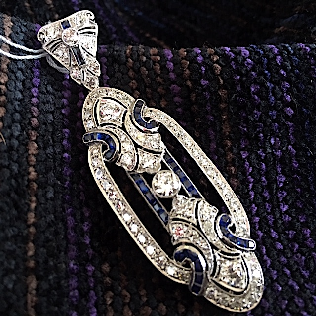 Highly sophisticated diamond and sapphire pendant that borders the Edwardian/art deco era, of the early 1900s. Elegant. Dramatic. And spectacular hanging from a fine gold chain or a strand of pearls.  RY Signature Collection. Price Group C.