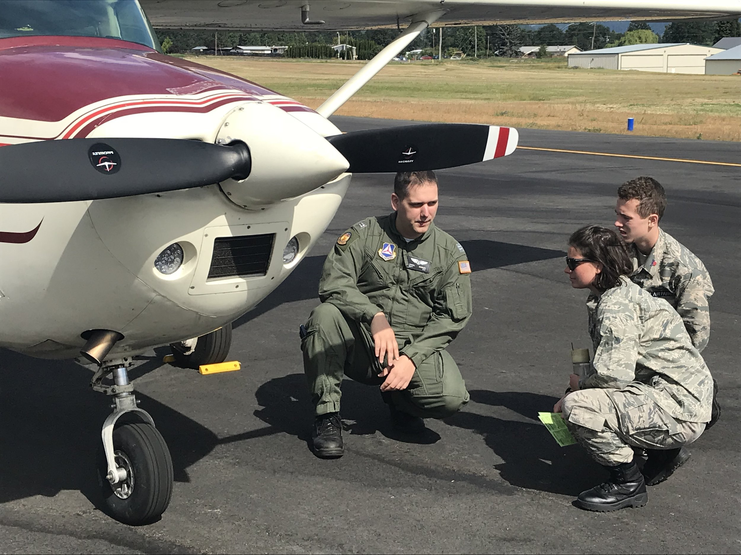 Cadets Victoria Ervin and Kalvin Young perform a pre-flight inspection with Capt. Daniel Bradley.
