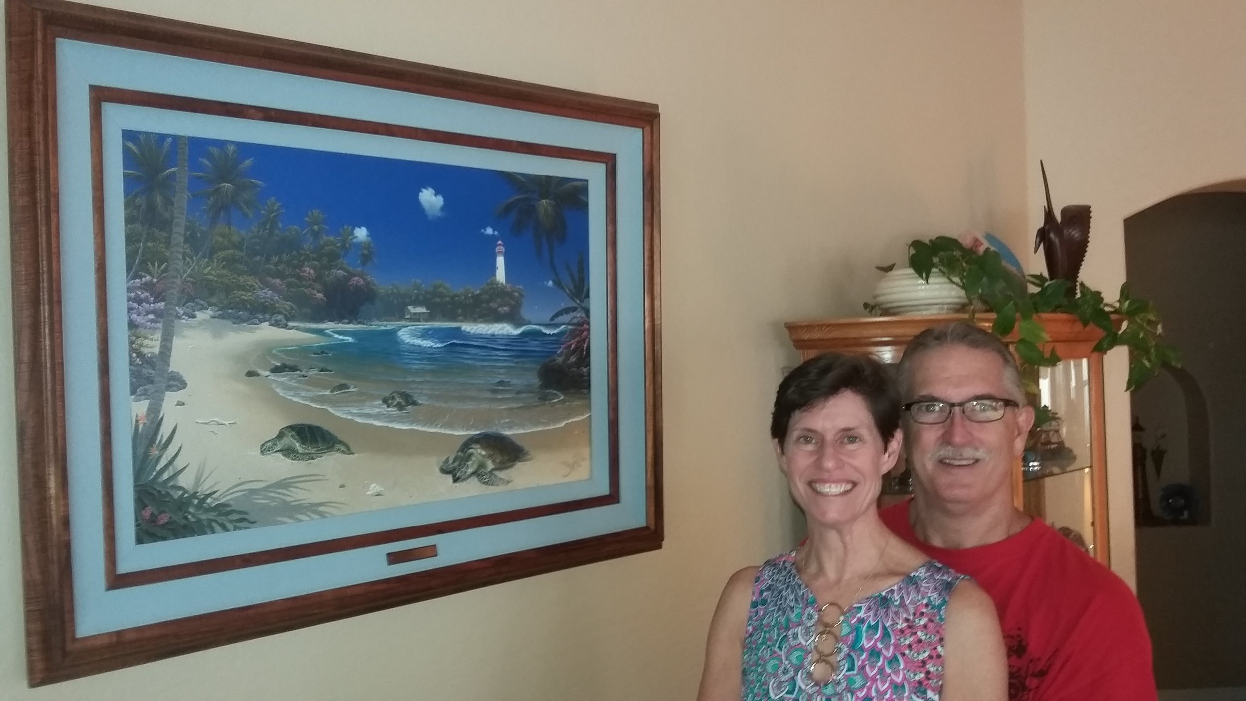 "Ron & Leanne Brewster with ""Turtle Bay""    We were first introduced to Al Hogue's work on a trip up the west coast in 2007. We fell in love with Tranquility Bay at a shop in Grants Pass Oregon but were unable to purchase the original at that time. We never forgot how much we really like the way he captured the beauty of the Hawaiian Islands. Ron then started a friendship with Al who was living in Hawaii at the time. We love anything to do with sea turtles and purchased from him a piece named ""Turtle Adventure"". The artwork is beautiful with the rich colors of the Hawaiian Islands and exquisite frame work of Koa wood. As the years past, Ron kept in touch with Al and exchanged news of our families. In 2018 we decided to have Al do a showcase piece for our home with our beloved sea turtles. He and Ron worked together to create the original, pictured here, ""Turtle Bay"". His use of color, light and the way he captures the feeling of the islands are what we love about his work. We will enjoy this truly magnificent piece of art for years to come.      R & L Brewster"