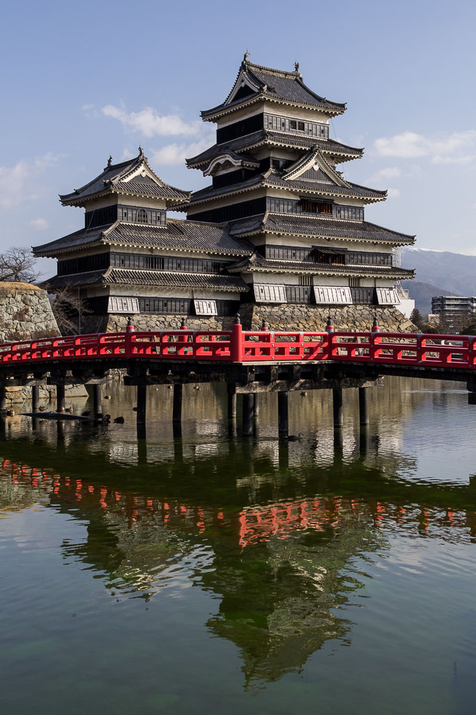 A contrasting red bridge spans the moat to Matsumoto castle.