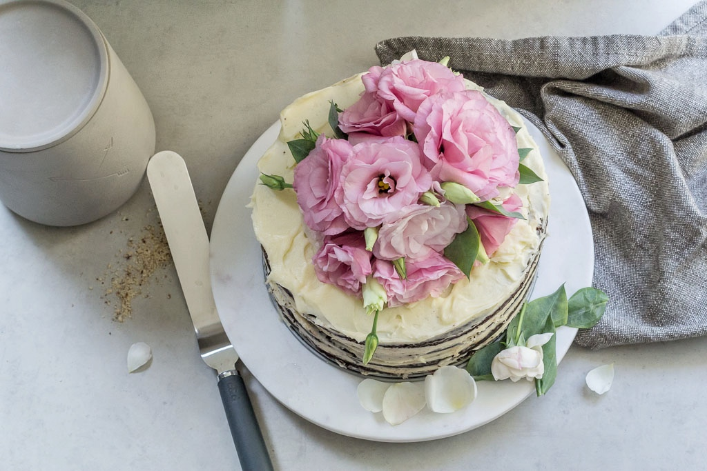 Flourless chocolate cake decorated with fresh flowers. Concrete canister and grey linen tea towel by Danica Studio from The Colour Society.