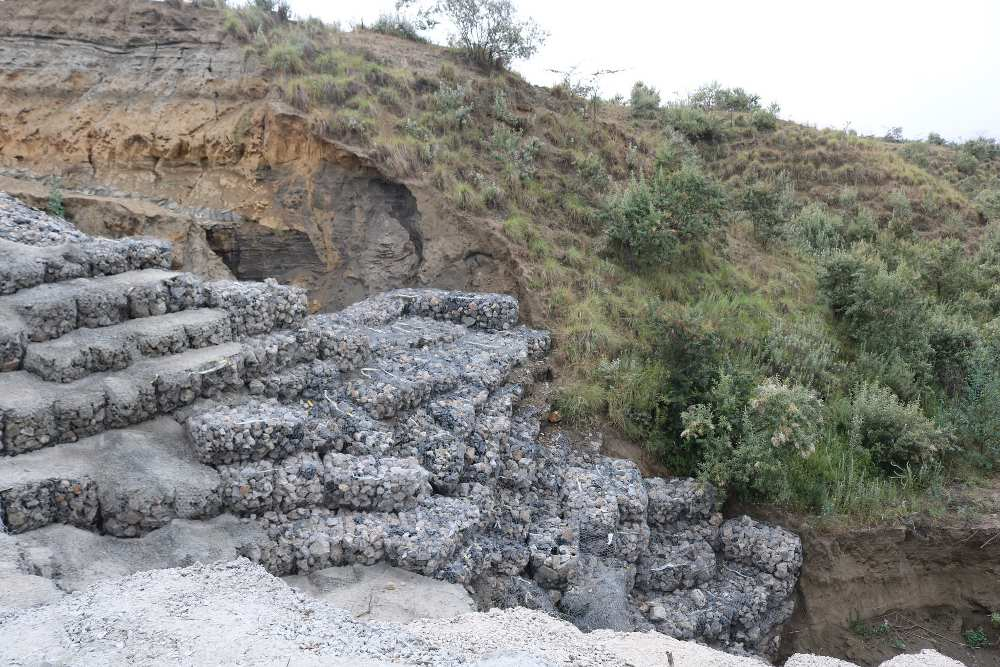 As well as being unfavourable for livestock-keeping, the hillsides where RAPland is located are susceptible to severe soil erosion. Numerous deep ravines bisect the village. These quickly fill up with fast-moving torrents during heavy rains, carrying away livestock, trees and whatever else is in their path. Gabions – cages filled with rocks, as pictured here – have done little to protect roads in the village from washing away, necessitating ever costlier repairs and reconstruction. Villagers speak of 'the hanging house' – a home in the village that was left 'hanging', or inaccessible, due to severe erosion of the road leading to it.