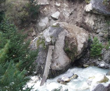 Bridge destroyed by flooding and landslide.